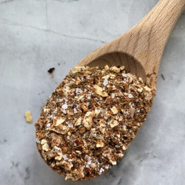 Top view of a wooden spoon on a marble countertop filled with seasoning.