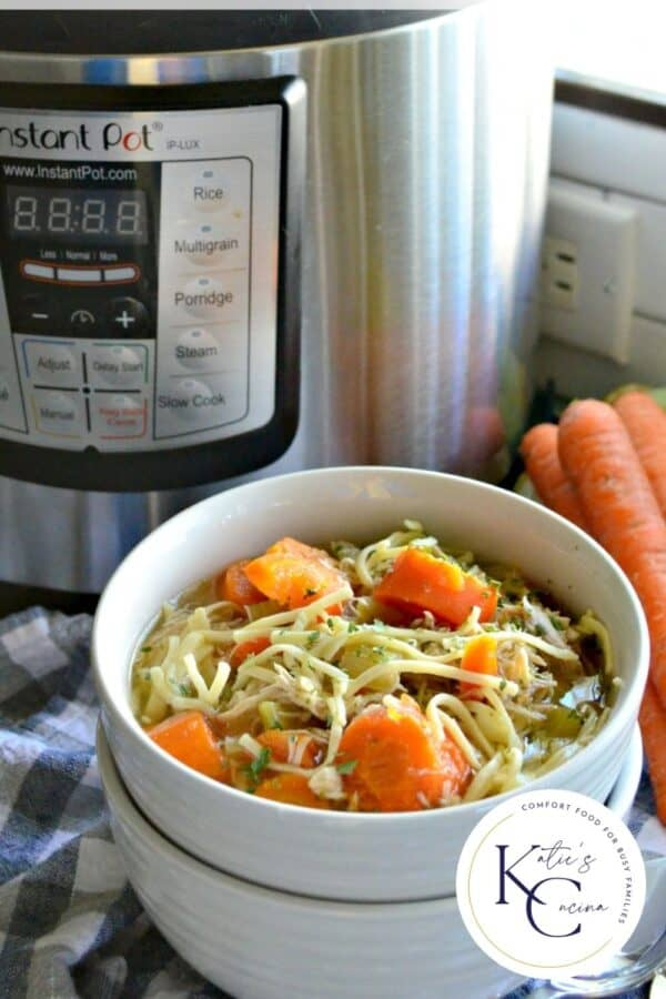 Two white bowls stacked with top bowl filled with chicken noodle soup with carrots and Instant Pot in the background.