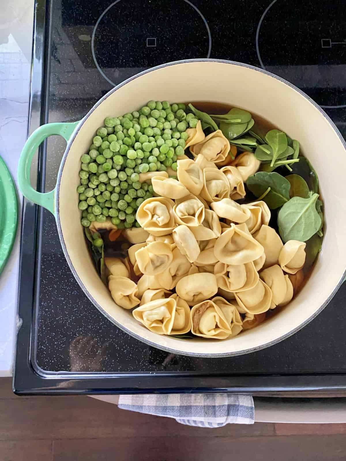 Top view of a green pot on a stove filled with tortellini, frozen peas, spinach leaves, and broth.