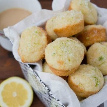 Tin basket lined with white cloth filled with mini muffins.