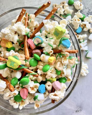 Top view of a glass bowl filled with a snack mix of popcorn, candies, and pretzels.