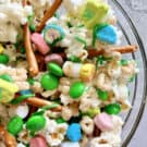 Close up of a glass bowl of popcorn, green M&M's, marshmallows, lucky charms, and pretzels.