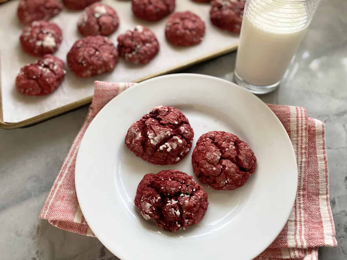 Three red cookies on a white plate with milk on the side.