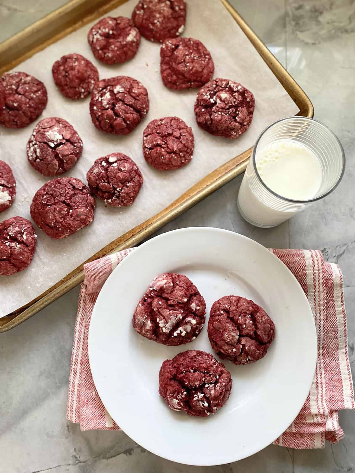 Top view of a baking sheet and white plate filled with red cookies.