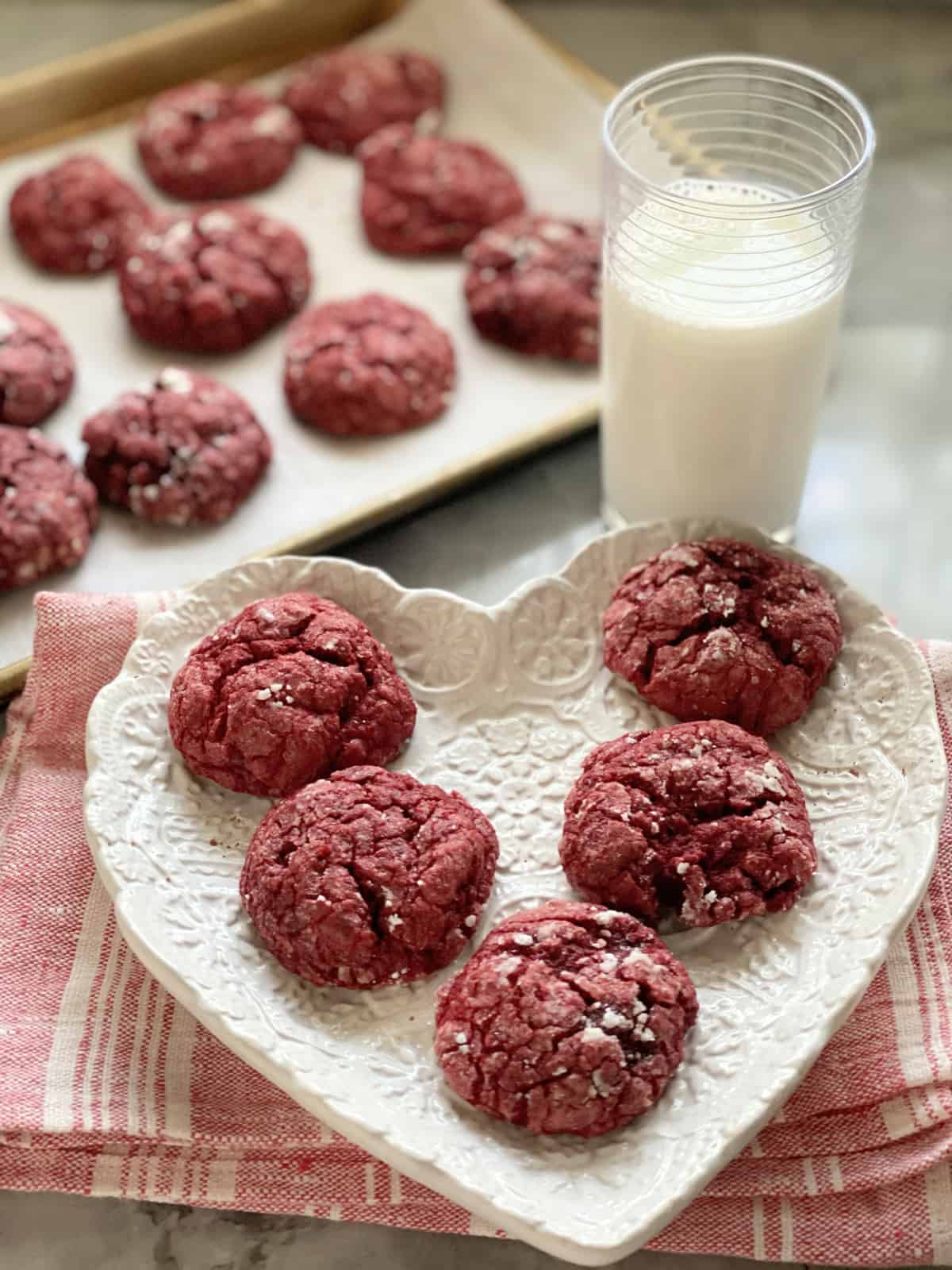 White heart shaped plate with five red cookies resting on it.