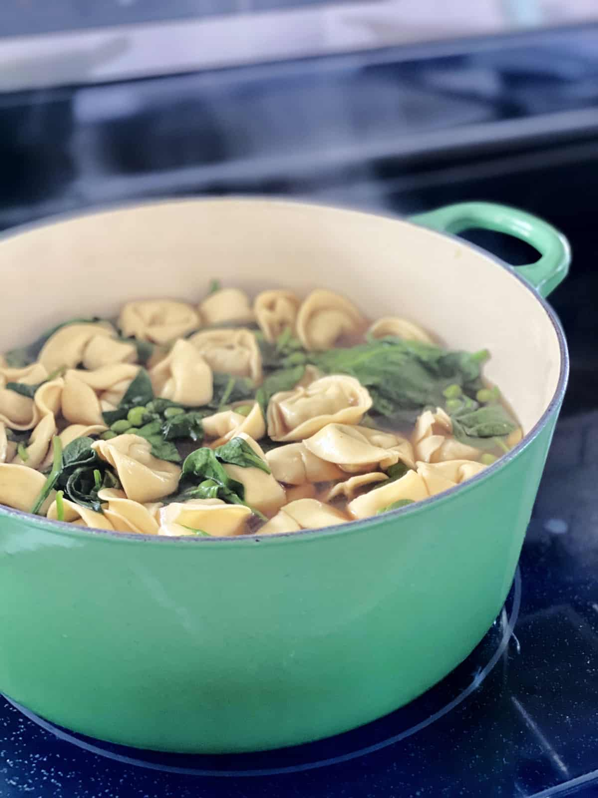 Green pot on a stove top with tortelini, spinach, and peas simmering with steam raised.