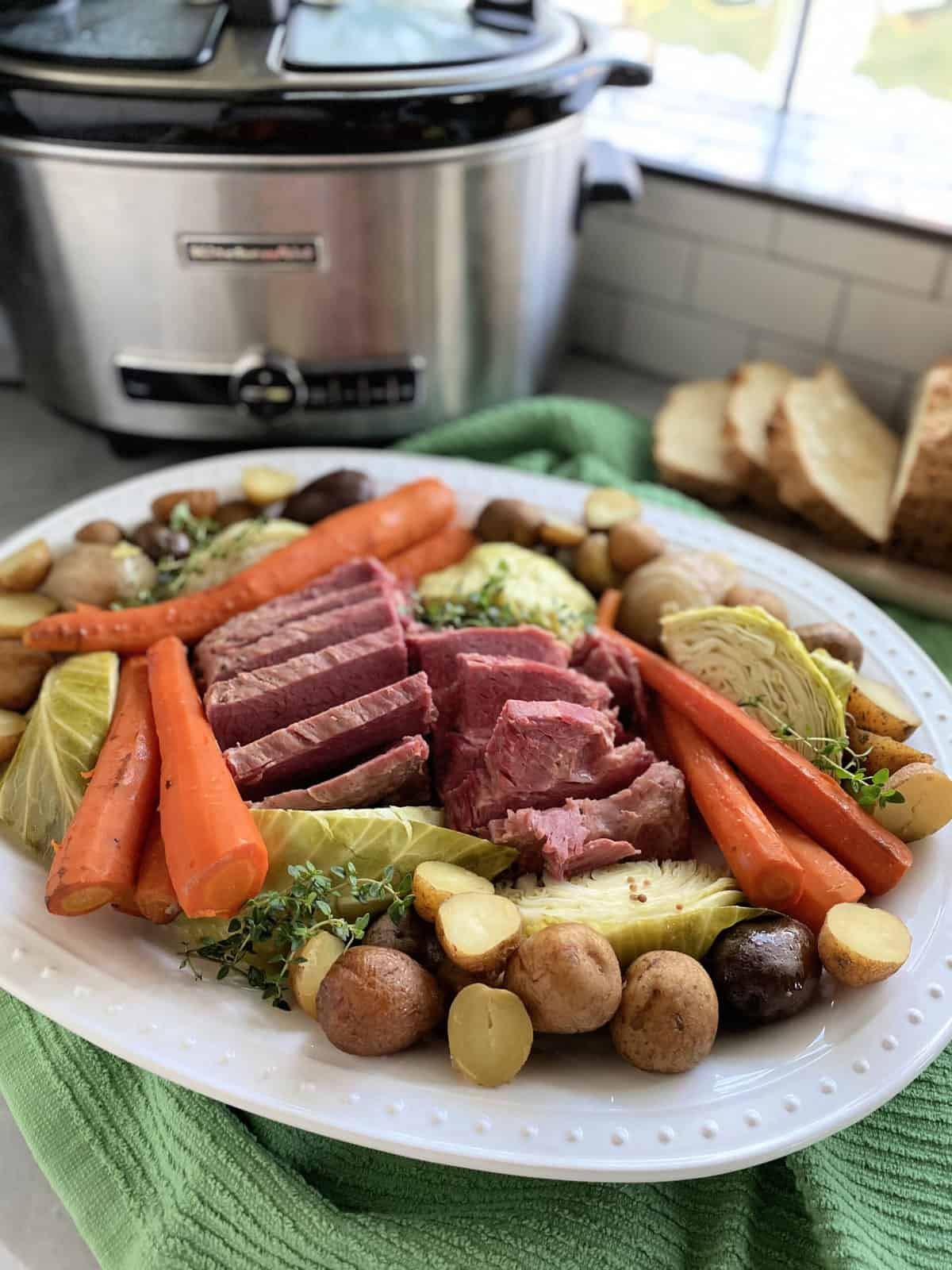 White platter filled with cabbage, corned beef, carrots, and slow cooker in the background.