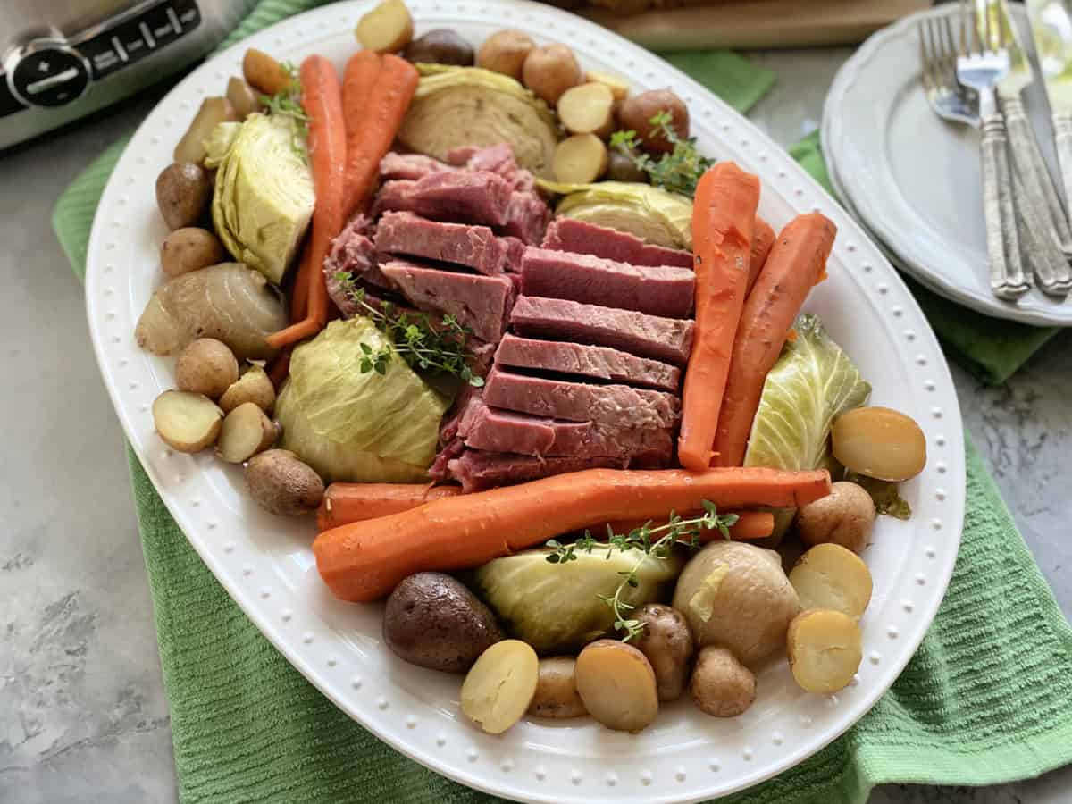 Top view of a white platter filled with meat and vegetables with plates and silverware on the side.