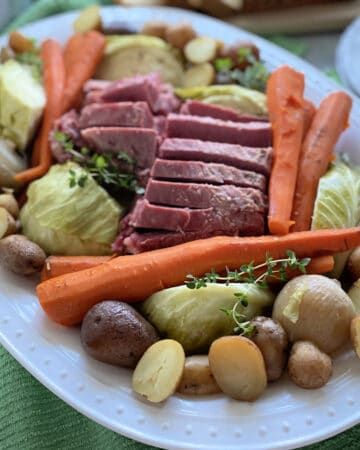 White platter filled with potatoes, carrots, corned beef, and cabbage.