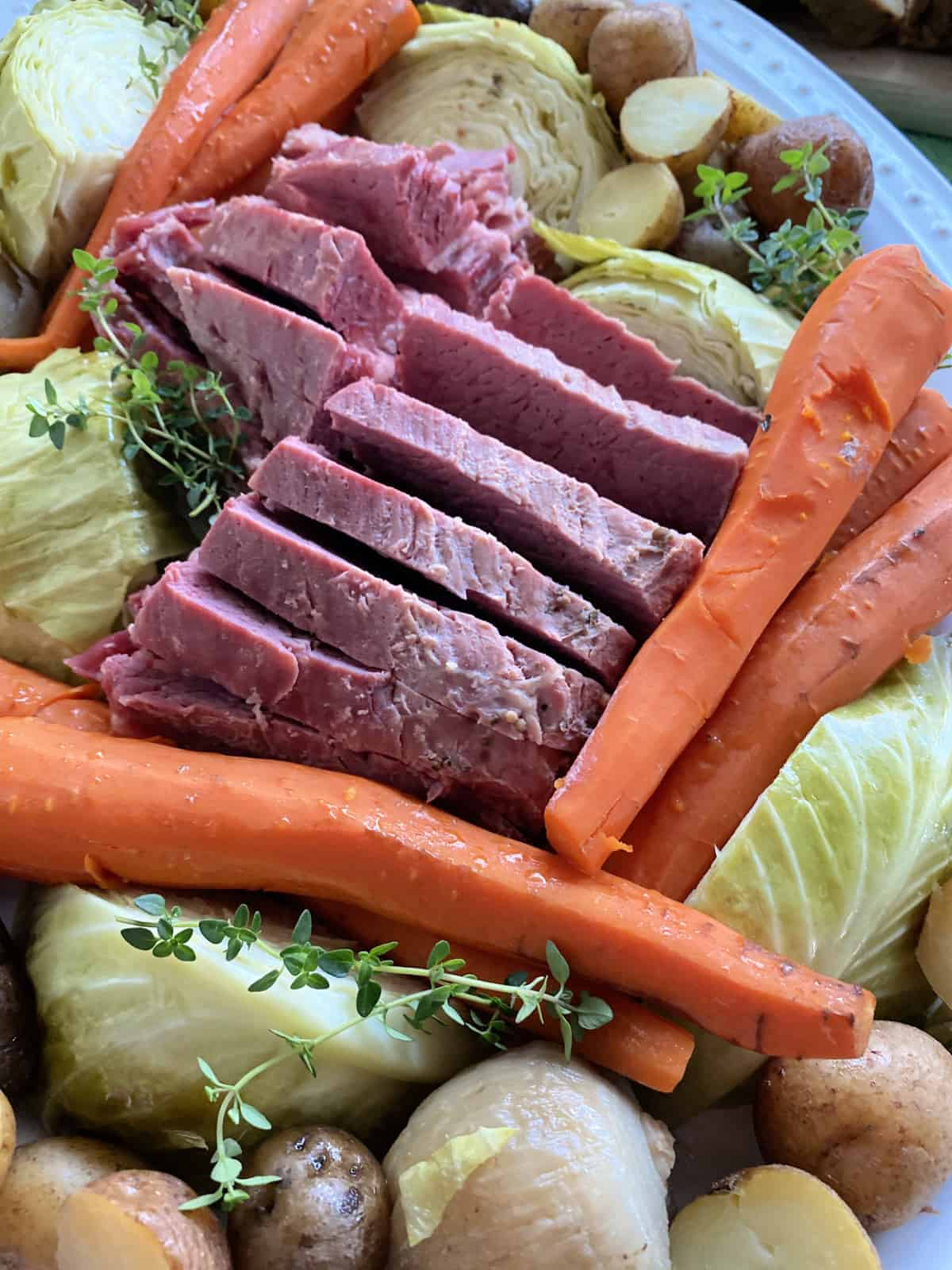 Close up of a platter of beef, carrots, cabbage, and potatoes.