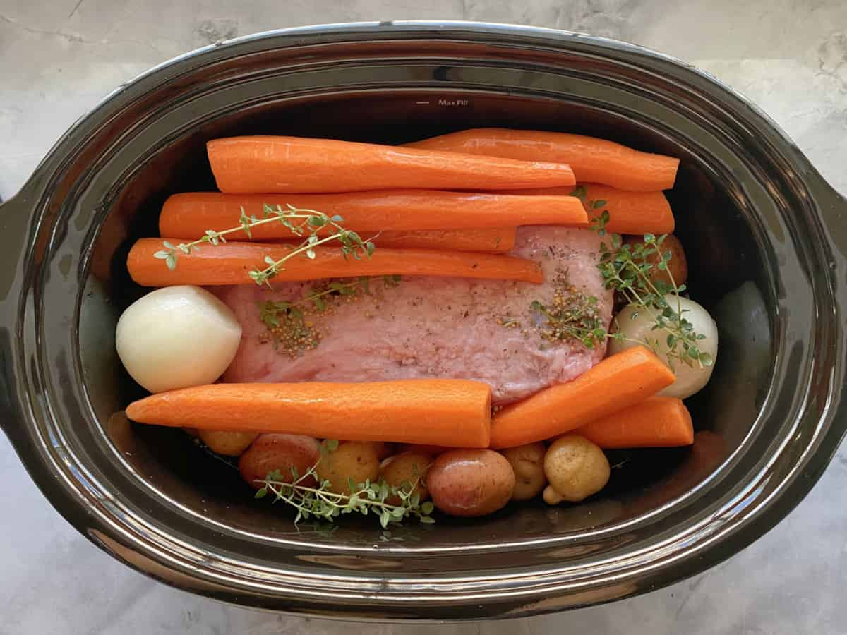 Top view of a slow cooker filled with carrots, onion, and beef.