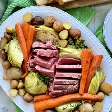 Top view of a white platter filled with beef, carrots, potatoes, and cabbage.