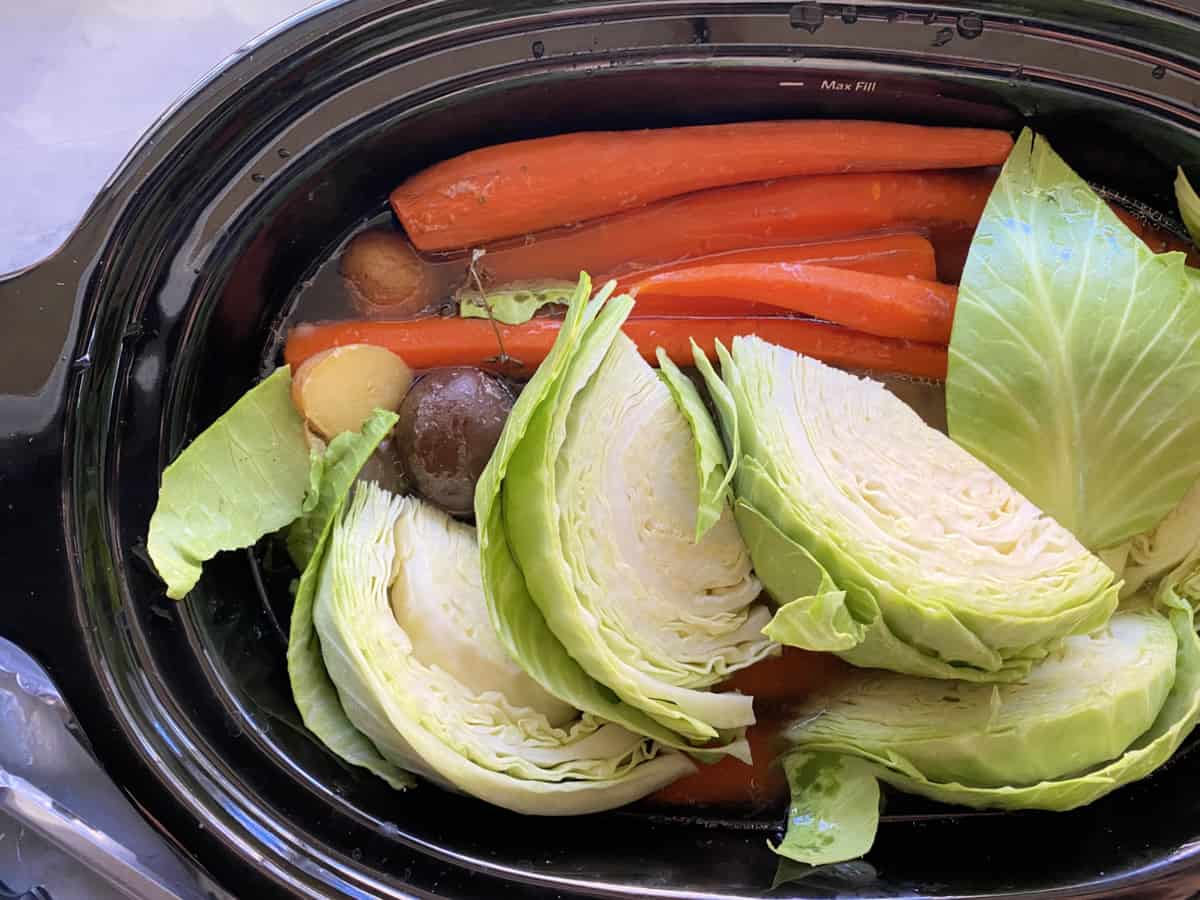 Top view of quartered cabbage, carrots, and potatoes in a black slow cooker.