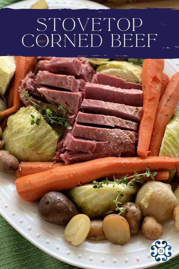 Close up of a platter of corned beef and cabbage with carrots and potatoes with text on top for Pinterest.