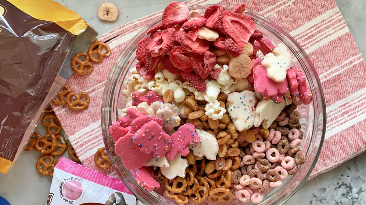 Top view of various snacks {pretzels, cheerios, popcorn, animal cookies) in a glass bowl.