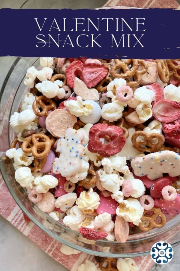 Top view of a glass bowl filled with red, pink, and white snacks with text on image for Pinterest.