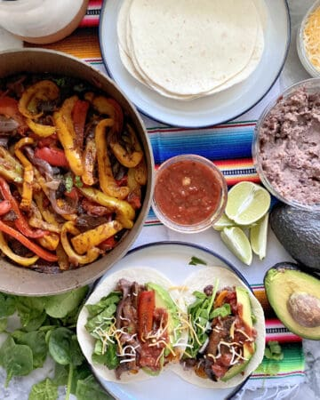 Top view of fajita peppers in a skillet, fajitas on a plate, and tortillas on the side.