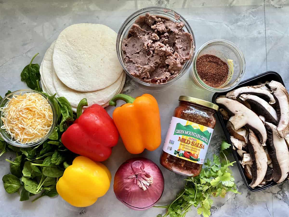 Ingredients on counter: tortillas, salsa, peppers, onions, mushrooms, fajita seasoning, cheese, spinach, black beans.