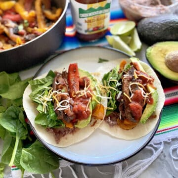 Two tacos on a plate with fajita peppers in the background.
