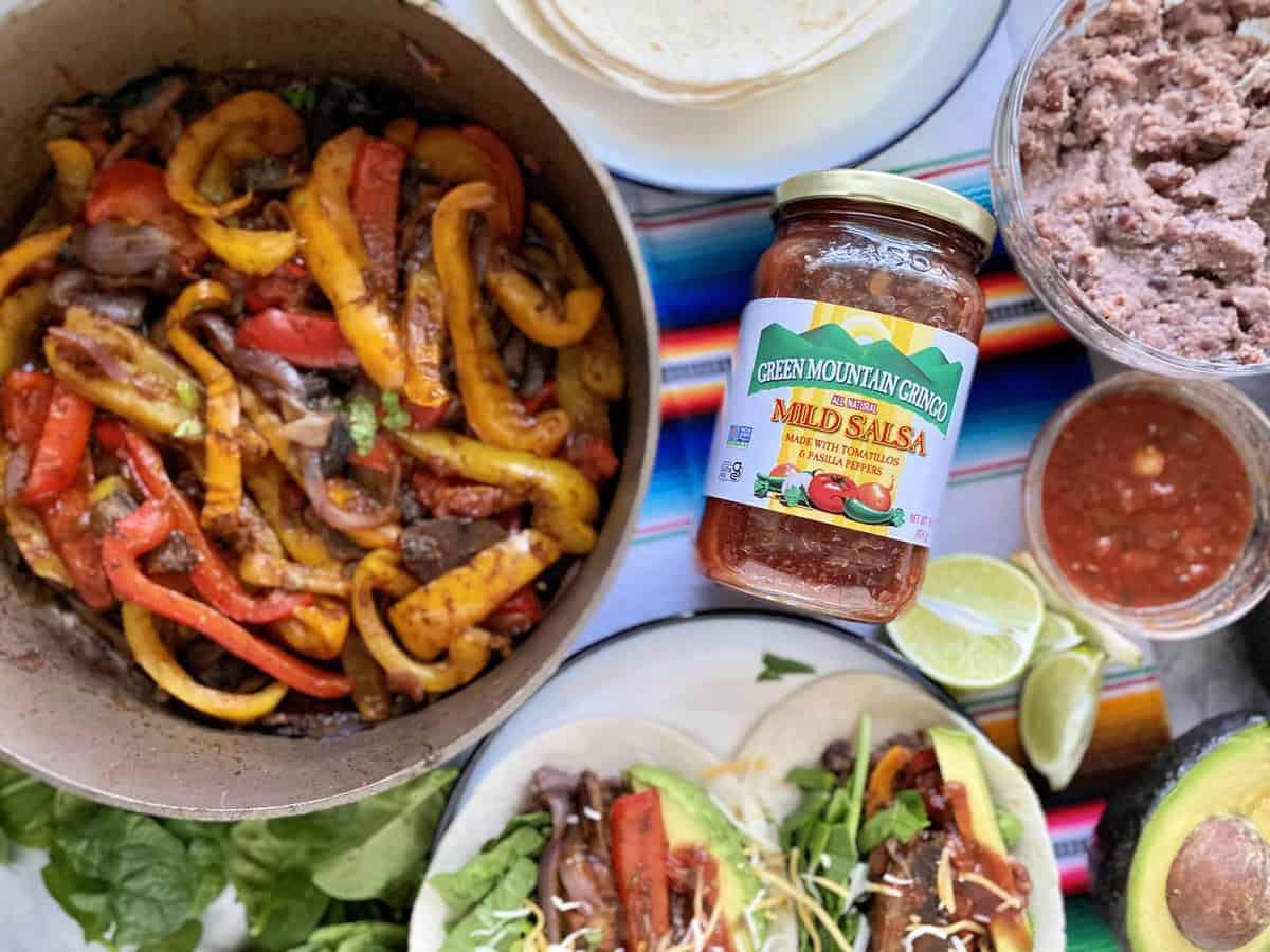 Green Mountain Gringo Salsa with fajita peppers and tacos around it.