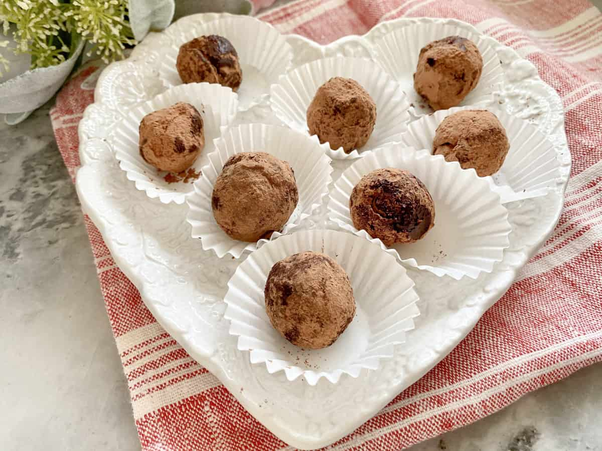 White heart shaped plate filled with 8 chocolate truffles.