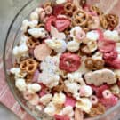 Top view of a glass bowl filled with various red, pink, and white snacks.