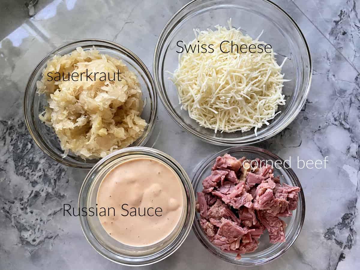 Ingredients on marble countertop: sauerkraut, swiss cheese, Russian sauce, and corned beef.