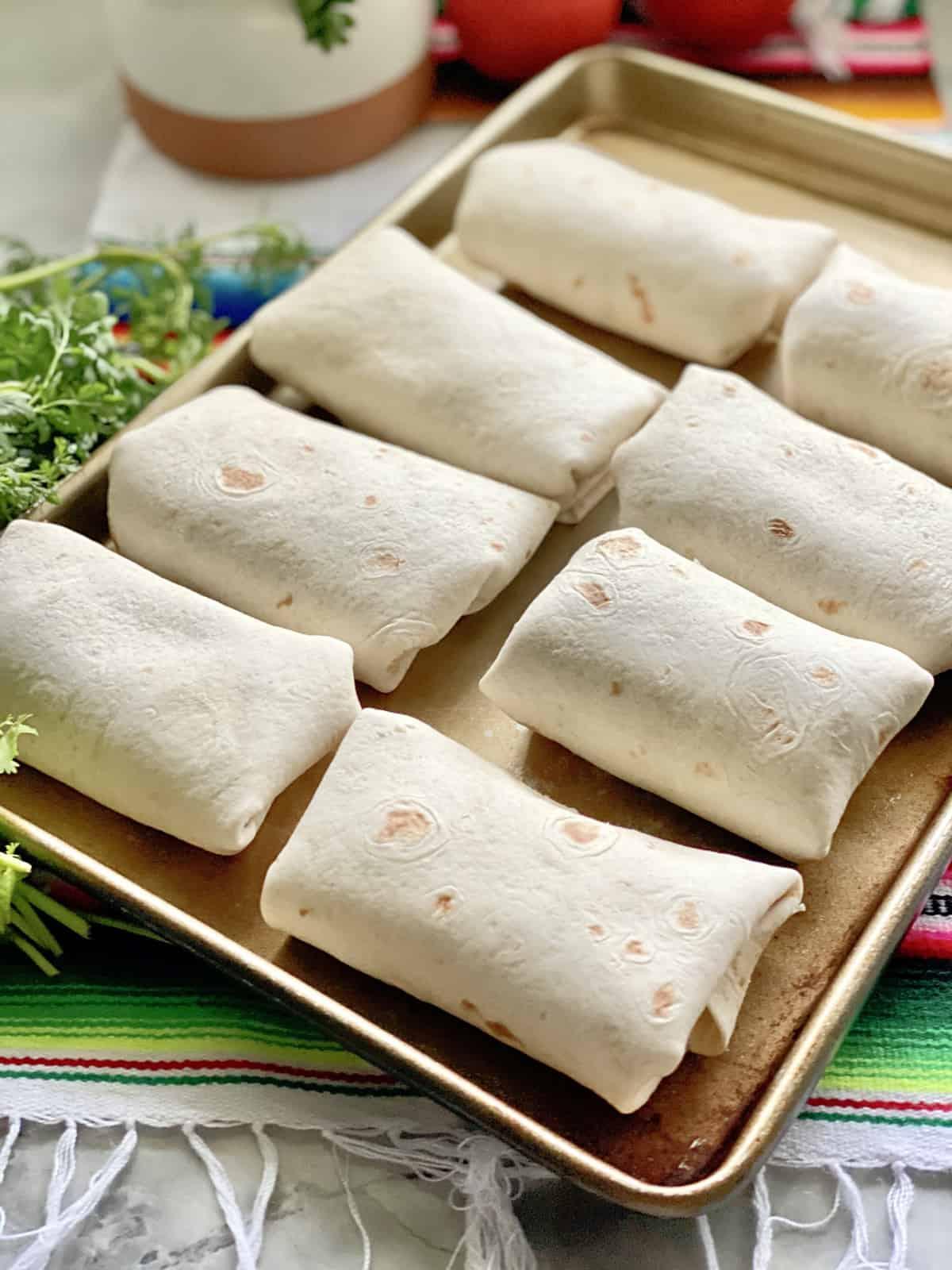 Baking sheet filled with 8 flour burritos.