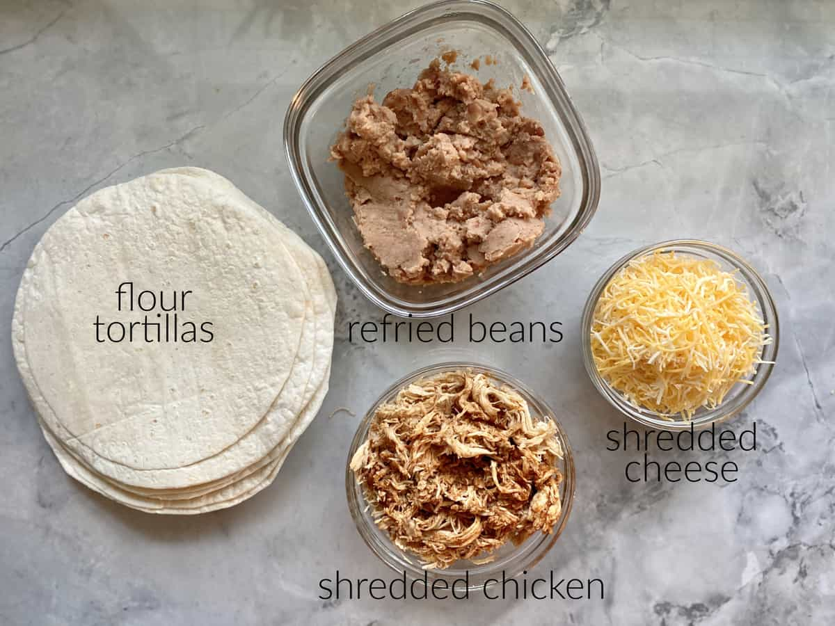 Ingredients on marble countertop: tortillas, refried beans, shredded chicken, shredded cheese.