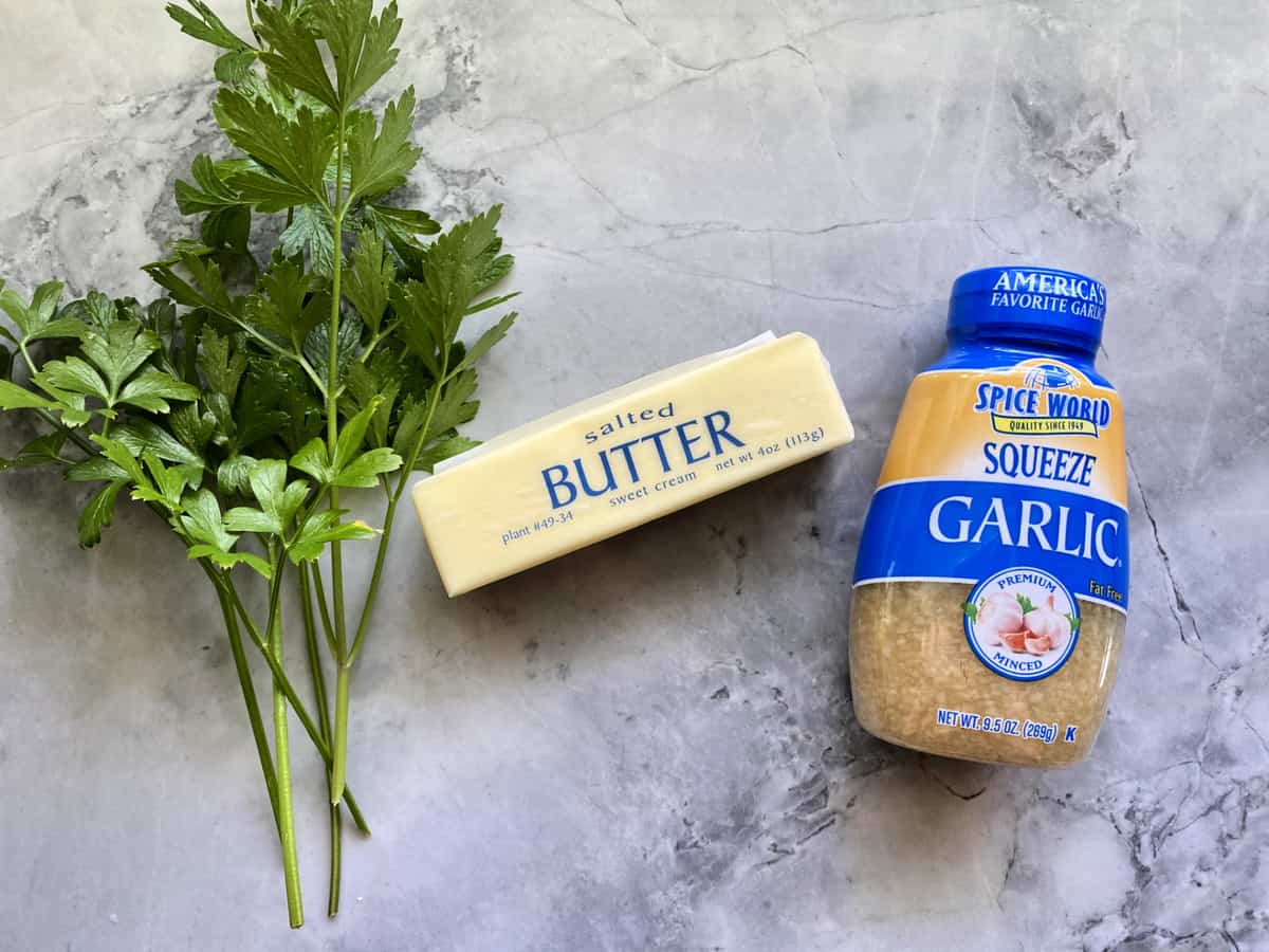 Ingredients on marble countertop: butter, garlic, and parsley.