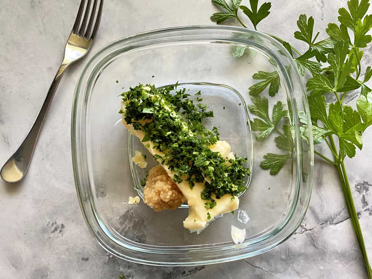 Square glass bowl filled with a stick of butter, minced parsley, and garlic.