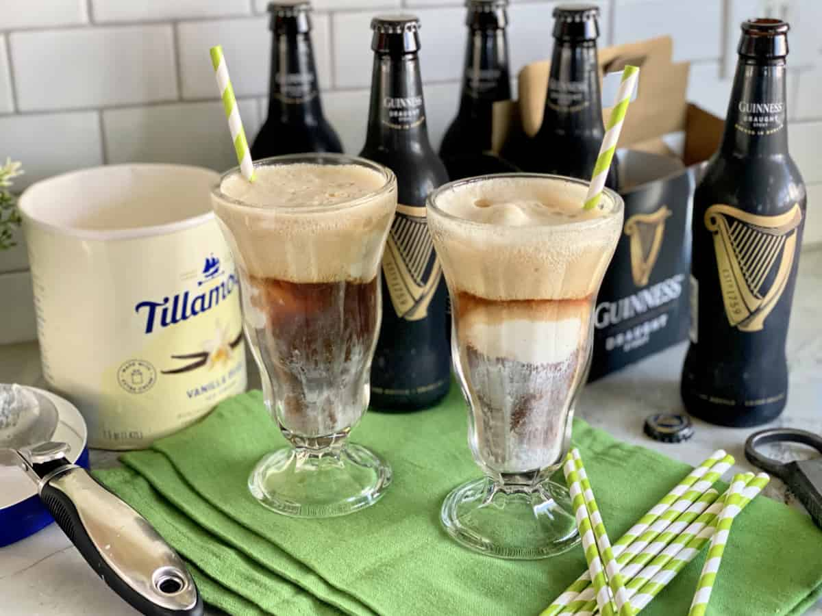 Two glasses filled with ice cream floats with Guinness beer in the background.