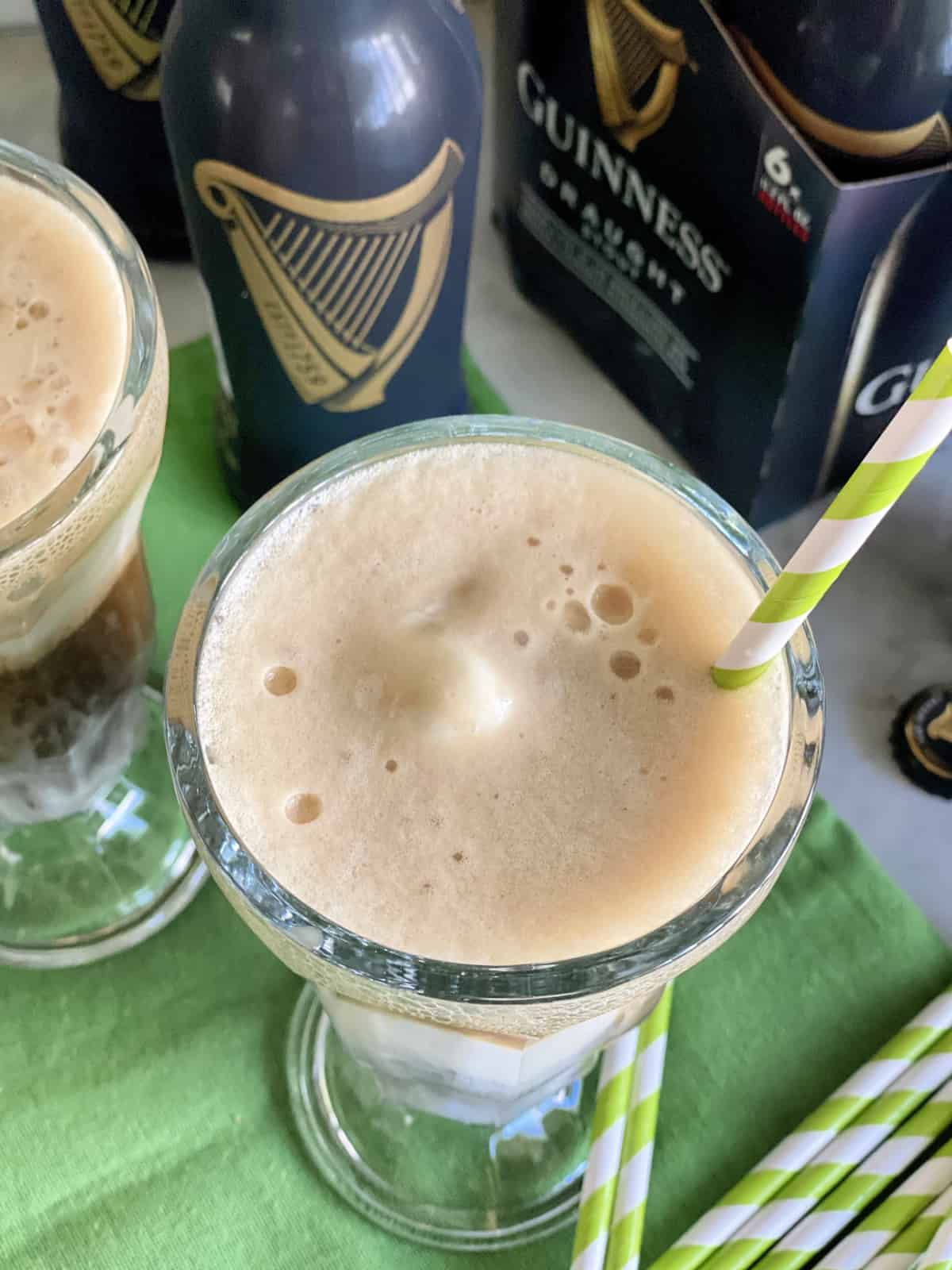 Top view of a beer float with a green and white paper straw.