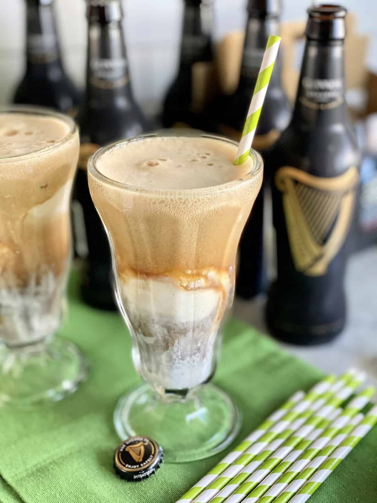 Close up of a glass filled with ice cream and Guinness beer with another glass and beer bottles in background.