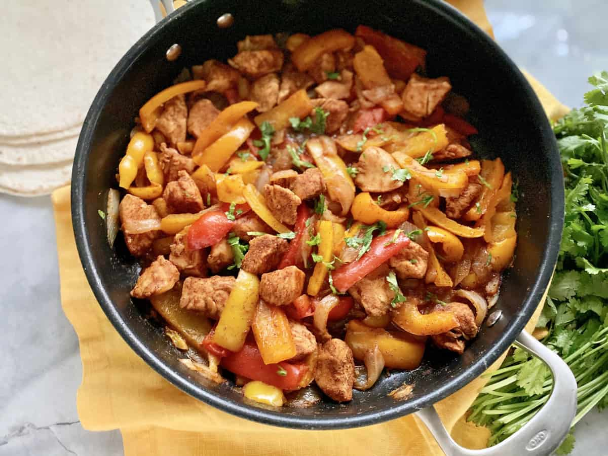 Top view of a skillet full of bell peppers and chicken on a yellow cloth with cilantro next to it.