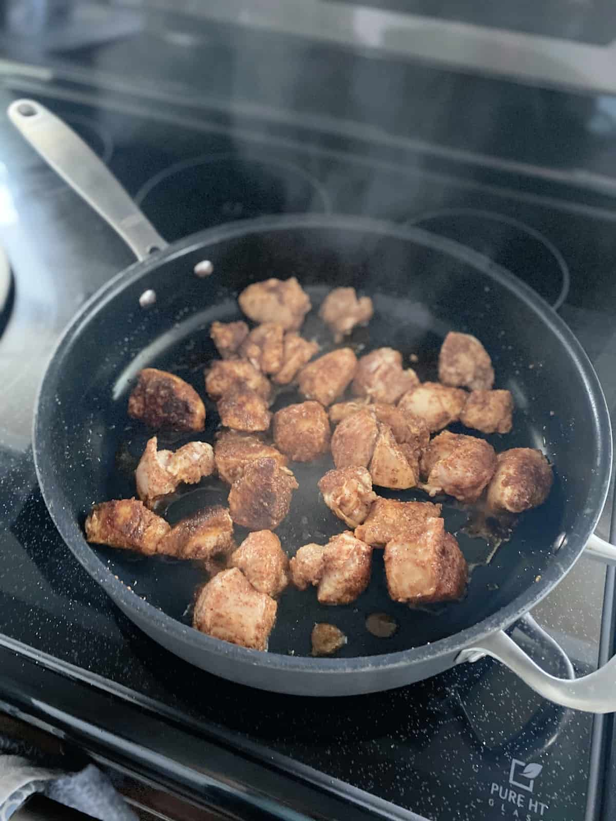 Skillet on a glass stove top cooking cubed chicken breast with seasoning.
