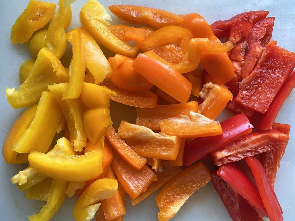 Yellow, Orange, and Red Bell peppers sliced on a cutting board.