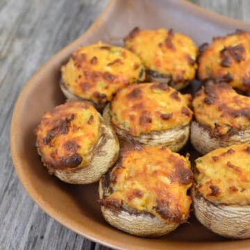 Brown baking dish filled with Buffalo Chicken Stuffed Mushrooms on a wood countertop.
