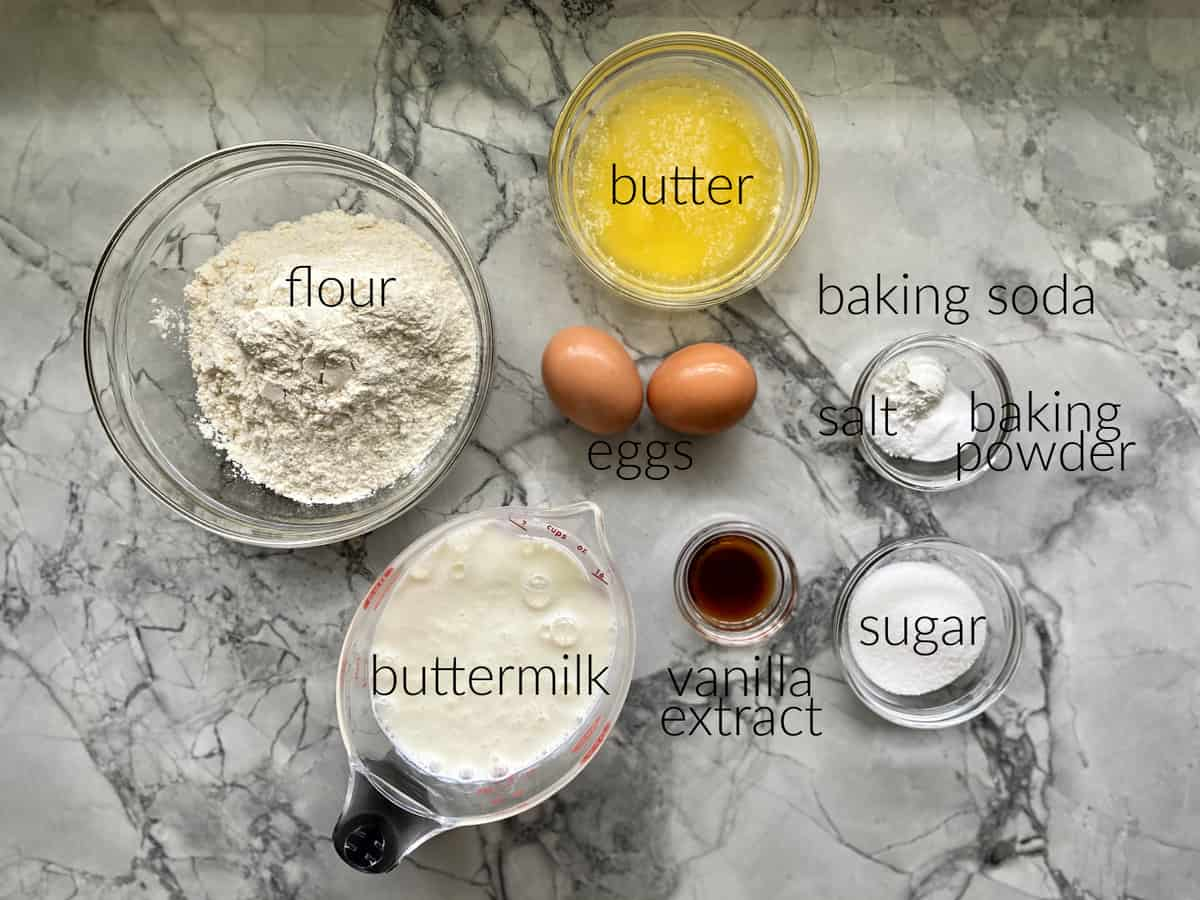 Ingredients on marble countertop: flour, buttermilk, butter, baking soda, salt, baking powder, vanilla extract, sugar, and eggs.