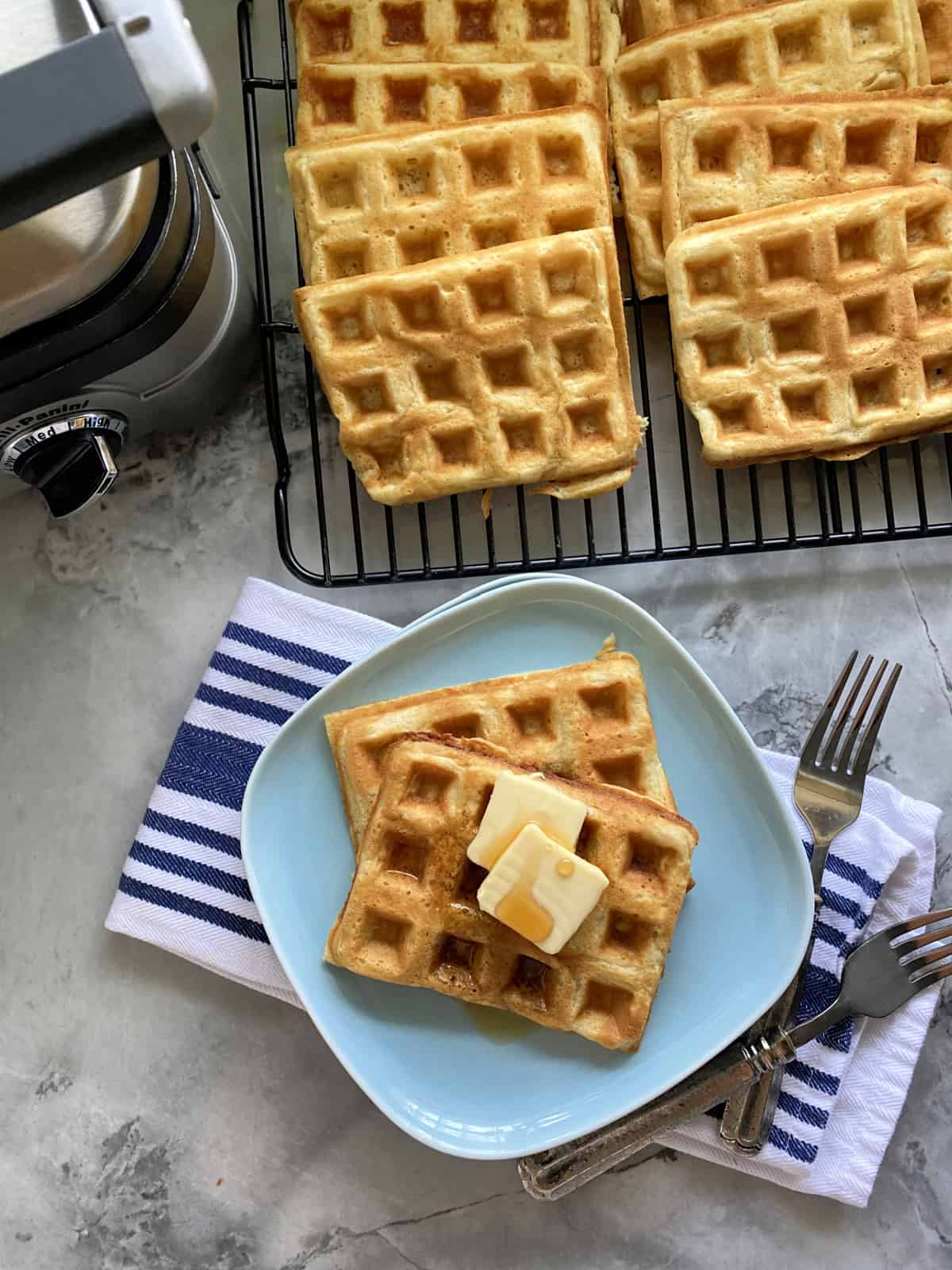 Top view of a blue plate filled with two waffles iwth butter and syrup with waffles and iron around it.