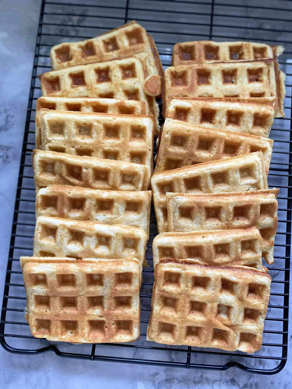 Top view of a black wire rack with rectangular waffles laid out on top of it.