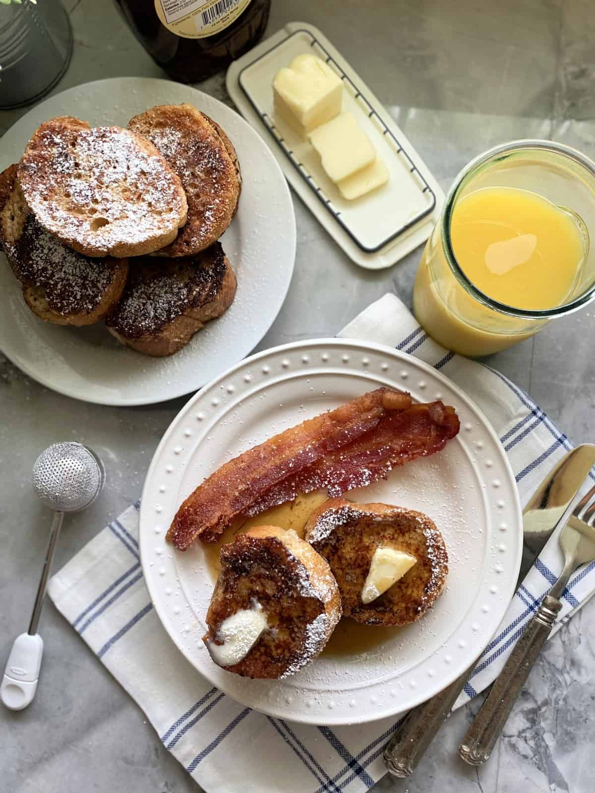Top view of a stack of french toast and another plate filled with french toast, butter, syrup, and bacon.