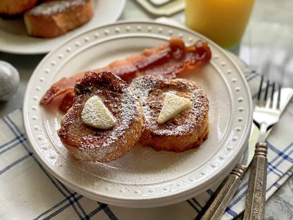 White plate filled with 2 slices of french toast with butter and syrup with bacon slices on white plate.