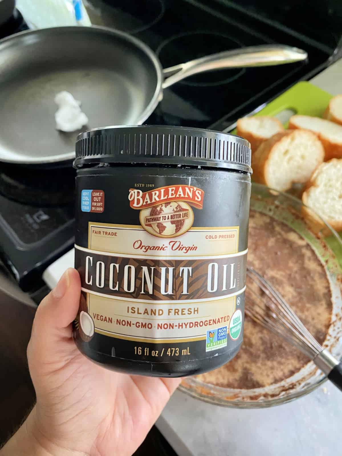 Hand holding Barleans coconut Oil with french toast supplies in background.