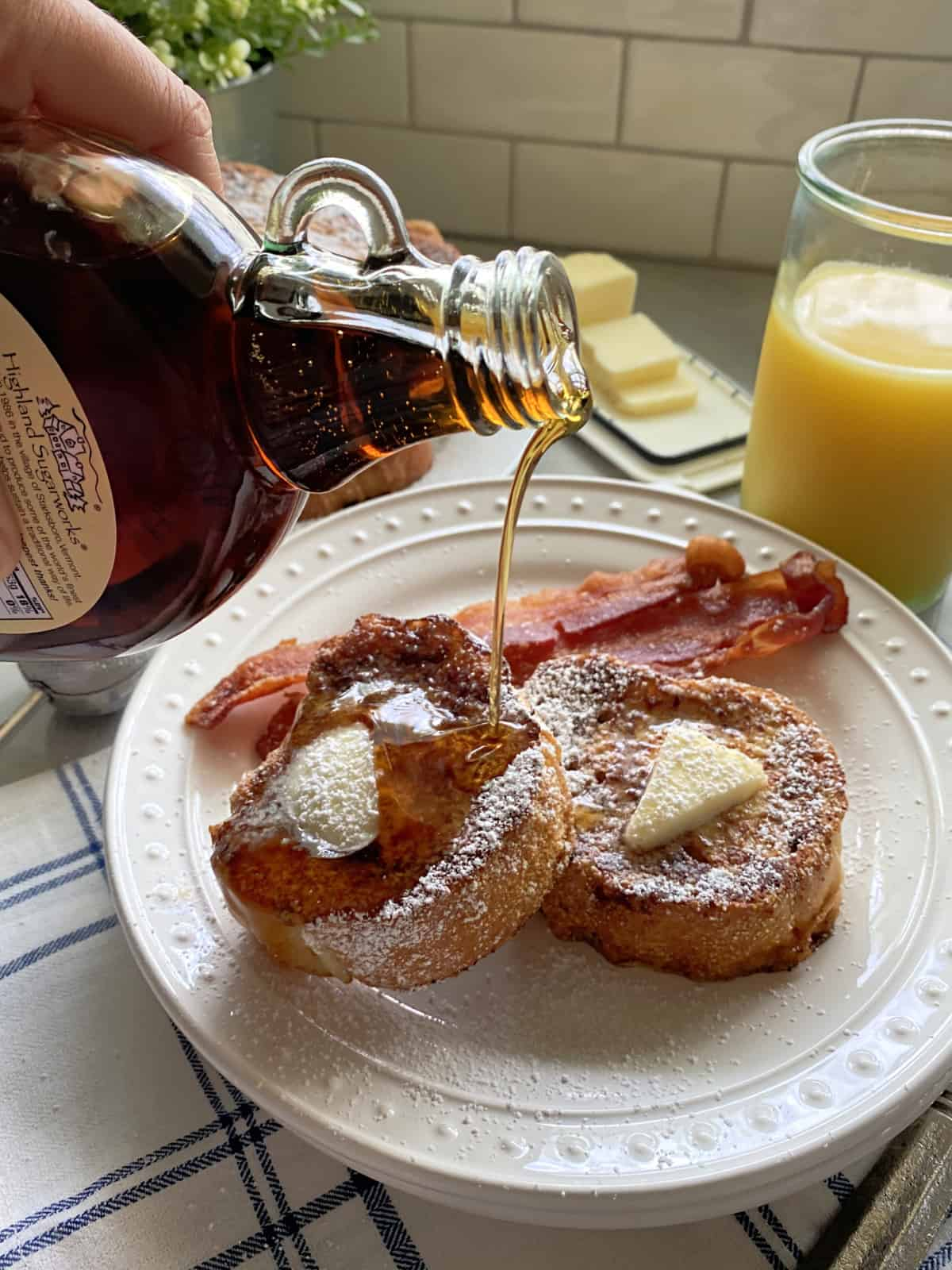 Hand pouring syrup over slices of french toast on a white plate.