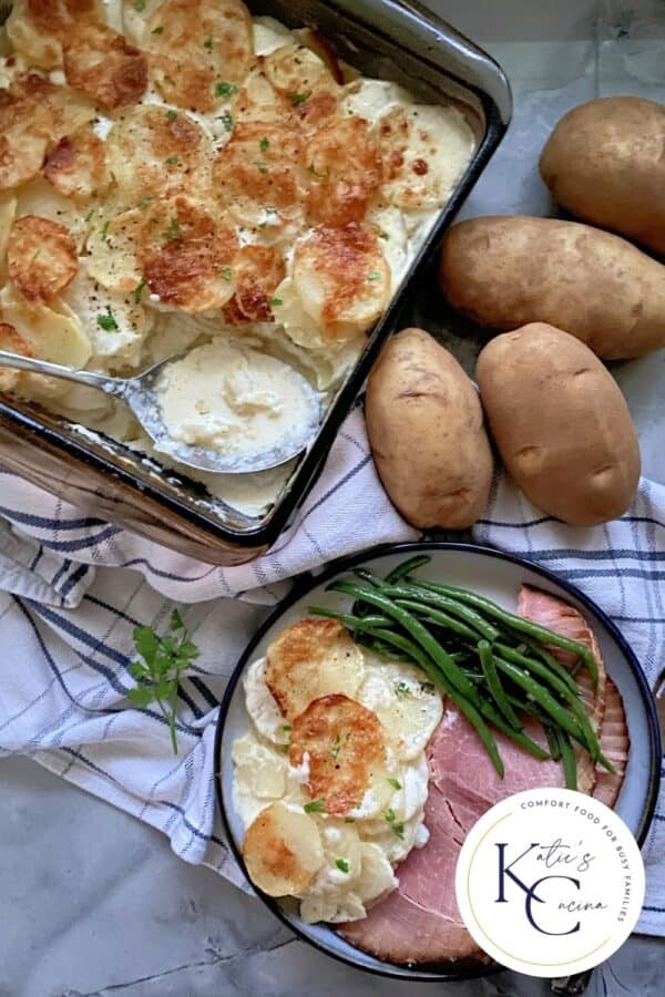 Top view of a baking dish filled with Gratin Dauphinois and a plate of ham, potatoes, and green beans.