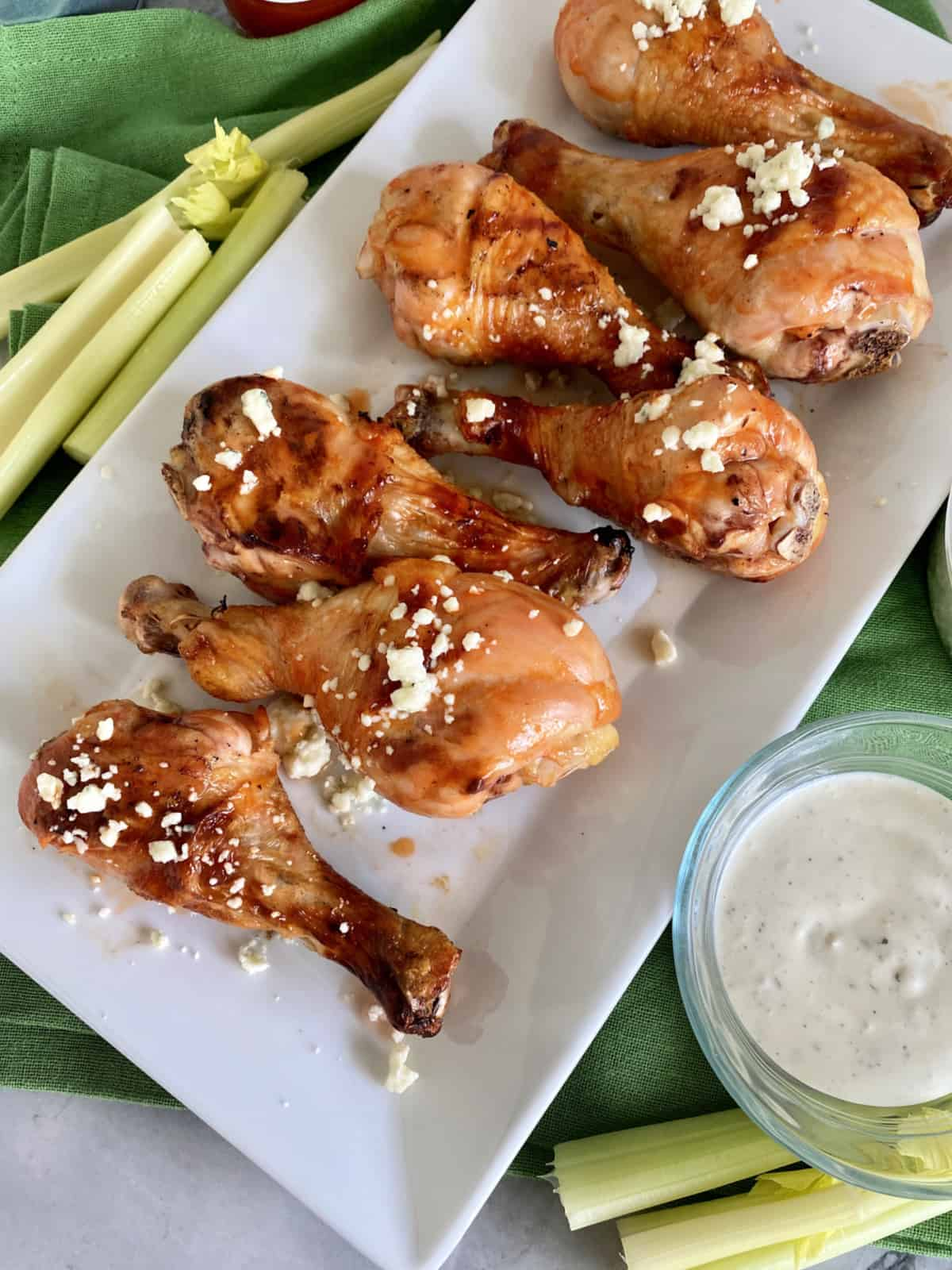 Top view of a white platter filled with Grilled Buffalo Chicken Drumsticks with bleu cheese.