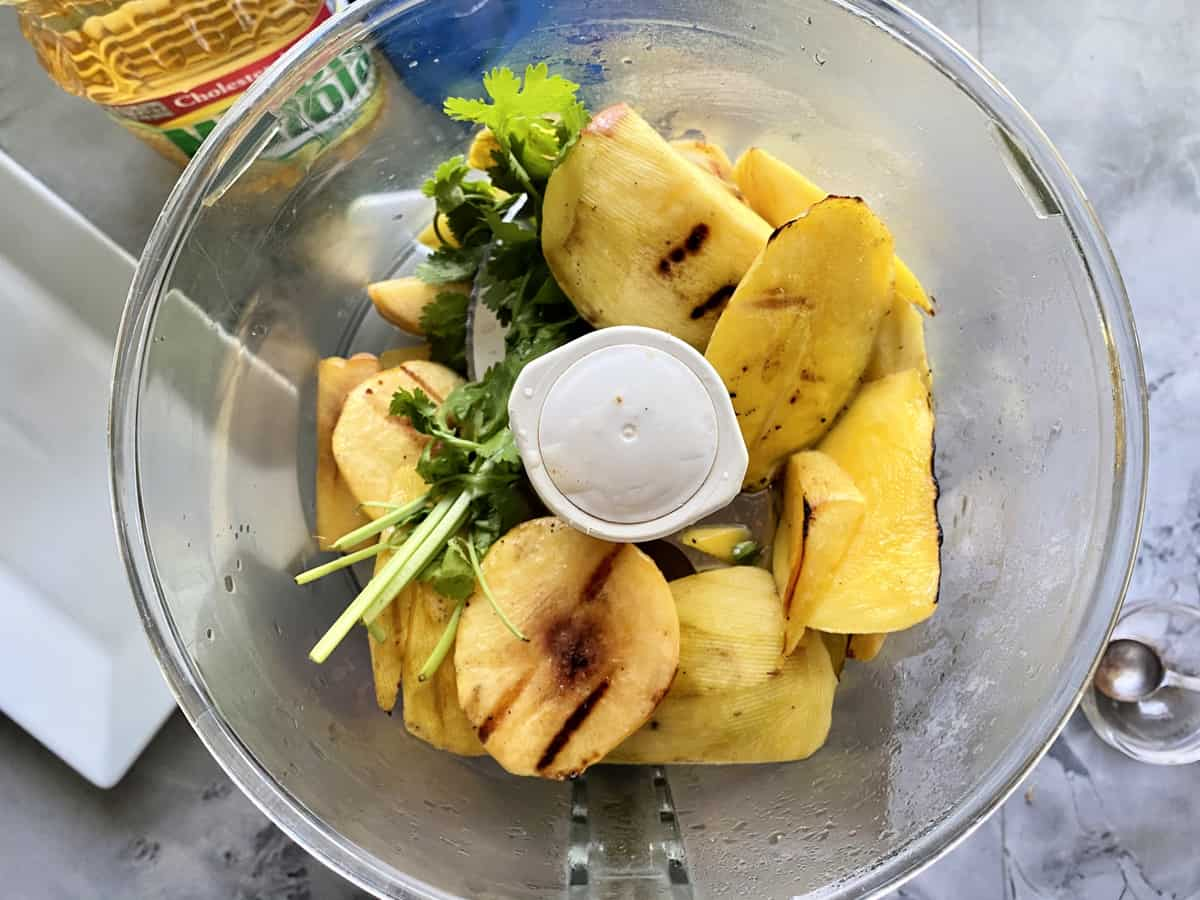 Top view of a food processor with grilled peaches and mangoes with cilantro.