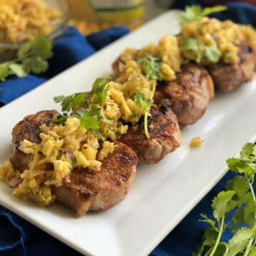 White platter with four pork chops topped with fruit salsa and cilantro on them.