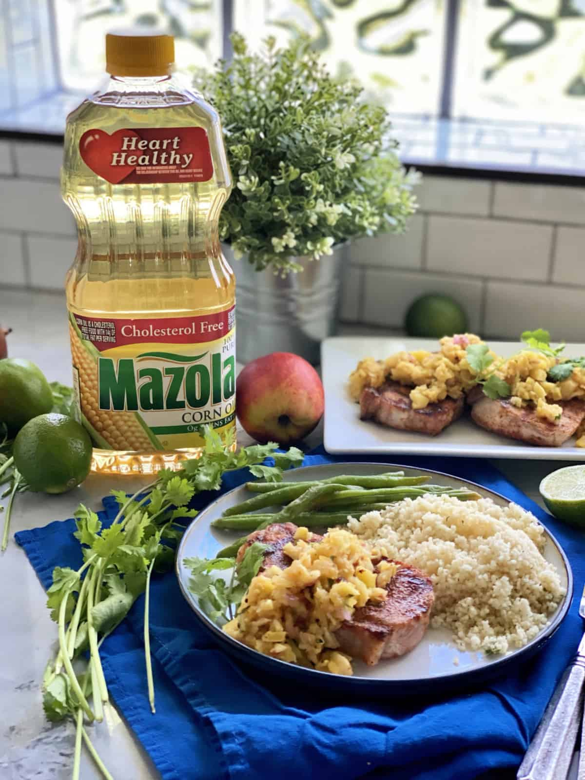 White plate filled with pork chops, fruit and couscous with a bottle of Mazola® Corn Oil in background.